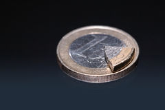 Dividend. Euro coin and coin's part lying on dark background Stock Photo