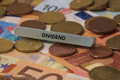 Dividend - het woord werd gedrukt op een metaalbar de metaalbar werd geplaatst op verscheidene bankbiljetten royalty-vrije stock afbeeldingen