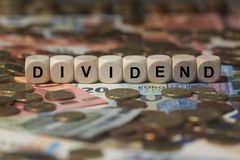 Dividend - kubus met brieven, de termijnen van de geldsector - teken met houten kubussen stock afbeeldingen