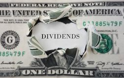 Dividends concept. Hole torn in a dollar bill with Dividends text royalty free stock photography