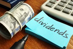 Dividends concept. Stack of dollars and calculator. With note royalty free stock image