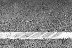 Dividing line with tire tracks over it Royalty Free Stock Images