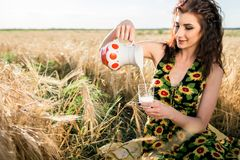 Girl in wheat field. Girl pours milk into a glass Stock Photography