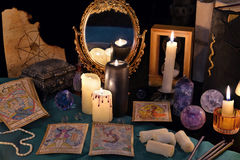 Divination rite with candles, the tarot cards, mirrow and crystals. Divination rite with candles, the tarot cards, mirror and crystals. Halloween concept, black Stock Photo
