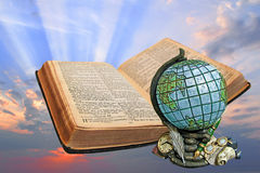 Divine bible spiritual light. Photo of open holy bible with office globe,clock,fountain pen,quill and spectacles with sunburst rays on background stock photography