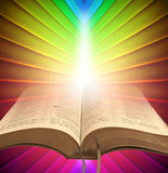 Divine bible spiritual light. Photo of open bible set against a rainbow background with divine light shining onto pages Royalty Free Stock Image