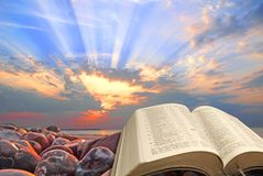 Divine bible spiritual light sun rays heaven sky god jesus miracles paradise. Concept photo of an open holy bible with sun rays in sky depicting divine spiritual stock image