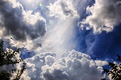 Divine clouds on a blue sky view from a garden stock photo