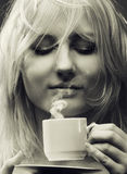 Divine drink. Young beautiful girl a blonde enjoys the divine aroma of coffee royalty free stock image