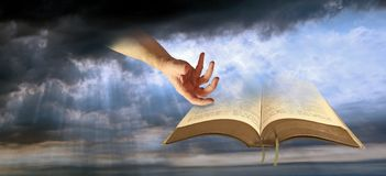 Divine hand of god open holy bible spiritual. Photo of divine hand of god presenting open holy bible depicting spiritual light for all mankind royalty free stock photography