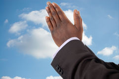 Divine Help. This is an image of businessman with hands in a prayer posture, seeking Divine Help or Divine Favor. The white glow round the fingers emphasises royalty free stock photography