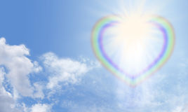 Divine Light. Heart shaped rainbow bursting with light on a blue sky background depicting divine love Stock Photos