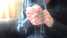 Divine light over hands of elder woman praying with rosary Royalty Free Stock Images