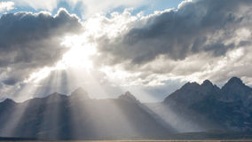Divine Light. Rays of sunlight break through the clouds onto the Grand Teton Mountain Range in Grand Teton National Park Stock Photo