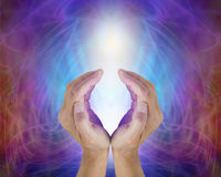 Divine Light Sacred Source of All That Is. Female cupped hands sensing the precious energy of All That Is, a glowing white light surrounded by an electric blue Stock Image