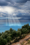 Divine light sky above sea. Divine light beams through storm clouds sky above turquoise sea royalty free stock images
