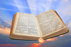 Divine light of truth bible. Photo of open bible at book of psalms with sunset sunburst rays in background Stock Photos