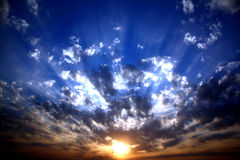 Divine Sunrise. Sunrays scattering through the clouds making it a divine scene, at sunrise stock image