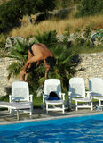 Diving in. Man in mid air jumping from diving board into outdoor pool royalty free stock images