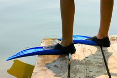 Before Diving. Detail of two male legs with blue swiming flippers Stock Photo