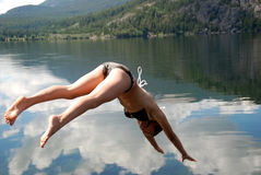 Diving. A woman diving into a lake stock photography