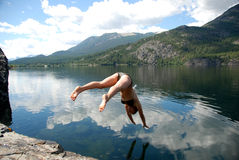 Diving. A woman diving into a lake in the mountains royalty free stock images