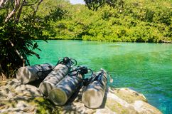 Diving air tanks close to the water. Bunch of diving tanks and green crystal water stock photography