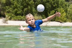 Diving for a ball in a lake Stock Photos