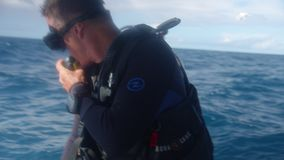 Diving on a blue wide sea. A medium shot of a man diving with his diving gear in a wide deep blue ocean stock footage