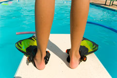 Diving Board. Child standiing with flippers on the end of a diving board at a swimming pool Royalty Free Stock Photography