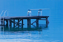 Diving board on a lake. Diving board on the edge of a calm water level Royalty Free Stock Image