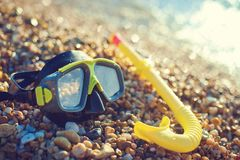 Diving concept - black mask and snorkel on Pebble beach Royalty Free Stock Image