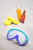 Diving concept - mask, slippers and suntan lotion bottles in san Royalty Free Stock Photo