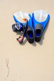 Diving equipment. Snorkel mask & flippers laying on the wild beach Stock Images
