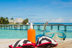 Diving equipment on the beach. Snorkel diving equipment and bikini on wooden pier by the ocean. Tropical paradise for diving Royalty Free Stock Image