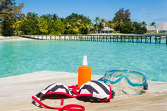 Diving equipment on the beach. Snorkel diving equipment and bikini on wooden pier by the ocean. Tropical paradise for diving Royalty Free Stock Images