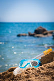 Diving equipment: mask and snorkel. Having fun at the sea: closeup of a diving mask and snorkel lying on a rock at the seashore Stock Images