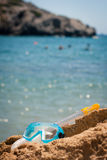 Diving equipment: mask and snorkel. Having fun at the sea: closeup of a diving mask and snorkel lying on a rock at the seashore (with people diving in the Royalty Free Stock Photos
