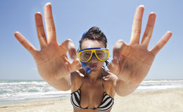 Diving girl in a swimming mask. Happy diving girl in a swimming mask and snorkel showing okay sign. Funny picture stock image