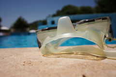 Diving glasses on poolside Royalty Free Stock Image