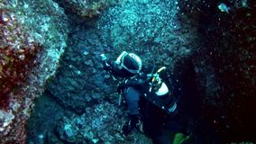 Diving in Mallorca Spain underwater - Diver leaving a cave stock footage