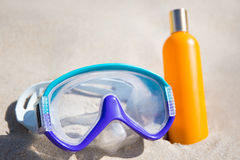Diving mask and bottle with suntan lotion on sandy beach Stock Image