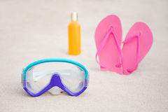 Diving mask, flip flops and suntan lotion bottle on sandy beach Royalty Free Stock Photos