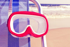 Diving mask hanging in a deckchair with a retro filter effect Royalty Free Stock Photo