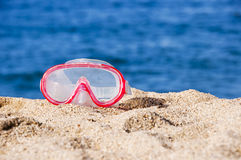Diving mask on the sand of a beach, blue water Royalty Free Stock Photography
