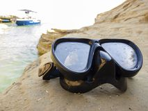 Diving mask for scuba diving on the rock near the sea.  royalty free stock photography