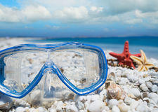 Diving mask and shells under clouds Royalty Free Stock Images