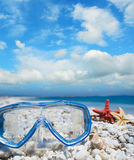 Diving mask and shells under clouds Stock Photo