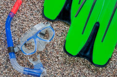 Diving mask with snorkel and fins on beach. Diving mask with snorkel and fins on background of stony beach Stock Photos