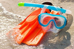 Diving mask, snorkel and fins on a sandy beach. Brightly colored diving mask, snorkel and fins on a sandy beach Royalty Free Stock Photos